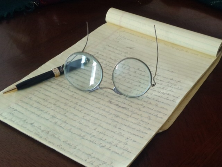 notepad with pen and wire-framed glasses