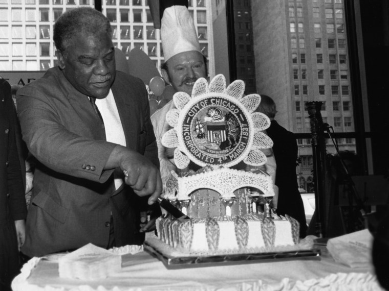 Mayor Harold Washington cutting a birthday cake for Chicago. Cake is elaborately detailed with a large city seal on top. Smiling man with a chef's hat is in the background.