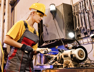Woman working on factory machinery