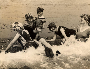 women in old-fashioned bathing suits splash in the surf