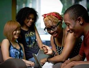 Teens gather around laptop