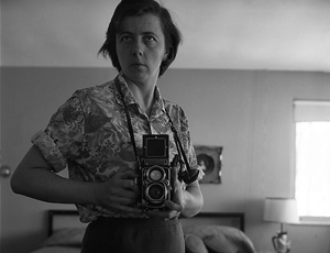 Woman with camera taking a photo in a mirror