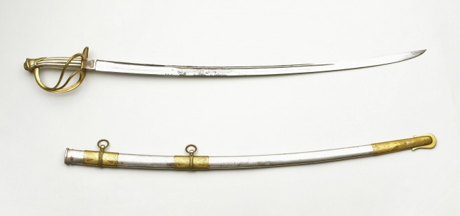 "The blade on this Civil War Cavalry Officers' Sword was made by the German firm, W. Clauberg for the New York company, Schuyler, Hartley and Graham (both names are engraved on either side of the ricasso). Schuyler, Hartley and Graham took on a variety of roles as a supplier of swords: assembler, wholesaler and retailer. The accompanying scabbard to this presentation sword is engraved: ""Presented to JB Finley, 1st Lieut. 14 Mich. Battery by his R.R. friends of Chicago, Aug. 1st, 1864."" In addition, the scabbard features an image of a steam engine pulling a train car."