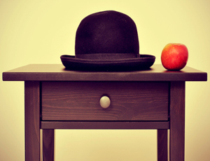 end table with bowler hat and an apple on top. Photo pays homage to surrealist artist Magritte