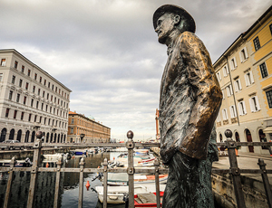 statue with buildings and boats in the background