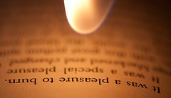 Match flame near book page