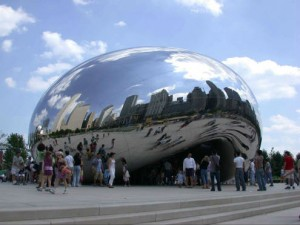 A crowd of people interact with Cloud Gate during Millennium Park's opening weekend. The Michigan Avenue street wall is visible in the background.