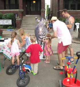 Children's Librarian Caleb Nolan helps neighborhood children play Pin the Tail on the Zebra