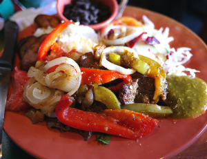 Plate Costa Rican food consisting of sauteed peppers, onions and beef with beans and salad