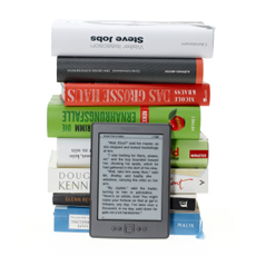 eReader in front of a stack of hardcover books