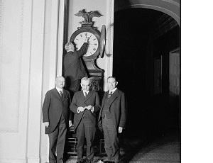 4 men setting ornate clock