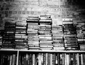 Books piled on bookshelf