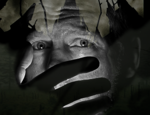 black and white photo of a scared man covering his mouth.