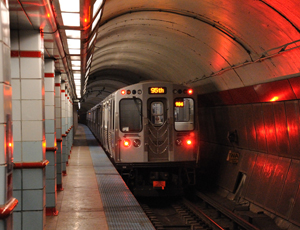 The back of a Red Line train leaving an underground station