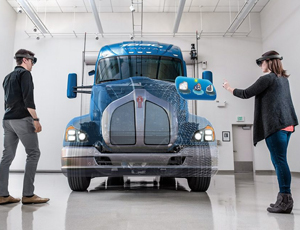 Two people wearing HoloLens look at a simulated screen in front of a semitruck