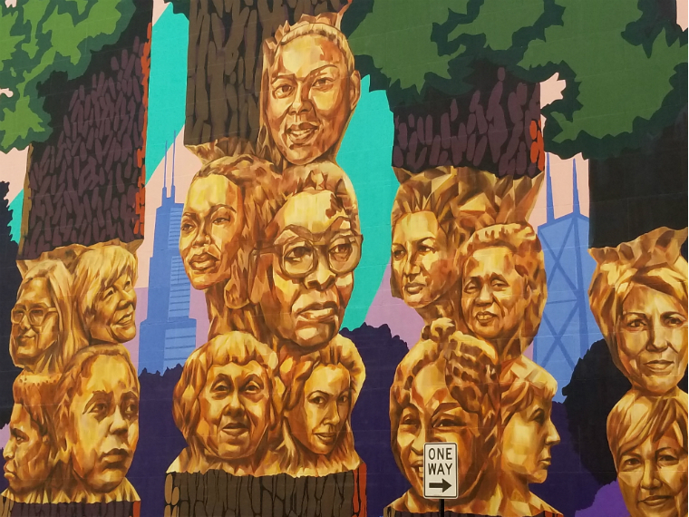 painting of twenty women's faces carved into tree trunks with skyscrapers in the background