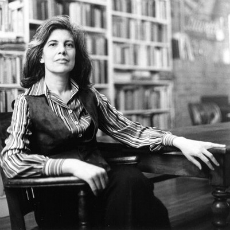 Susan Sontag sitting in wooden chair at wooden table with bookshelves in the background